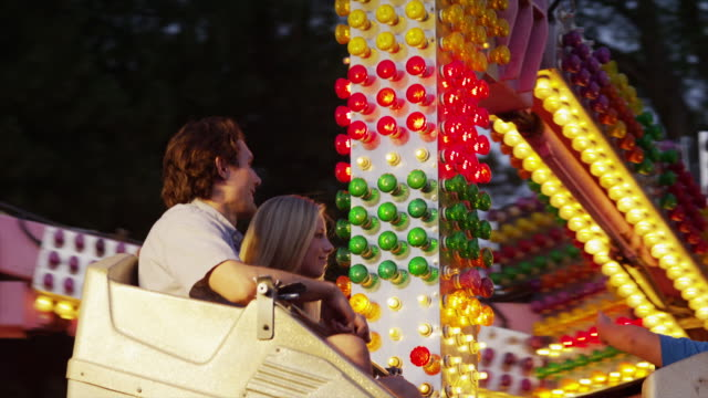 tracking shot, medium shot of young couple on amusement park ride / american fork, utah, united states - tre quarti video stock e b–roll