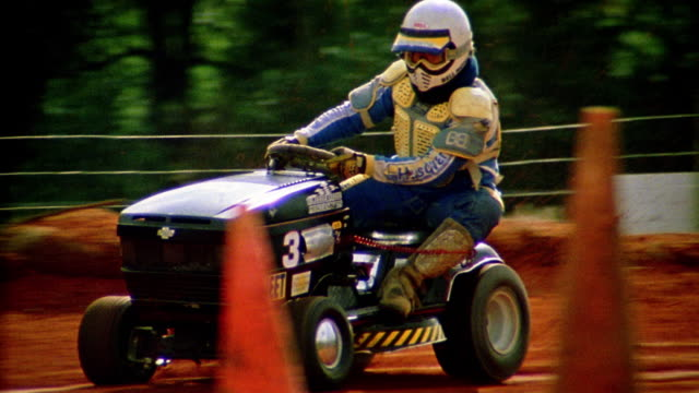 tracking shot men wearing full racing gear and riding lawn mowers on dirt track / alabama - tagliaerba video stock e b–roll