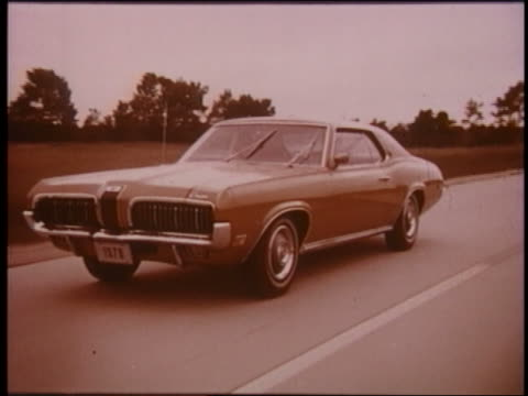 1970 tracking shot mercury cougar with windshield wipers going driving on country road - 1970年点の映像素材/bロール