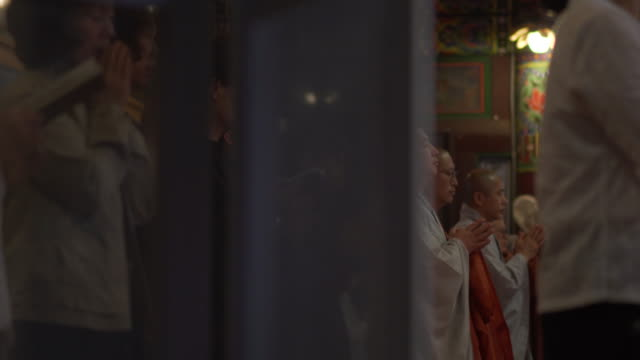 tracking shot, monks pray in temple - buddhismus stock-videos und b-roll-filmmaterial