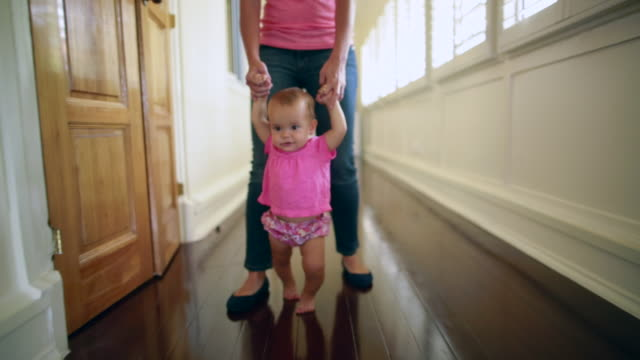 Tracking shot mother walking with baby girl at home.