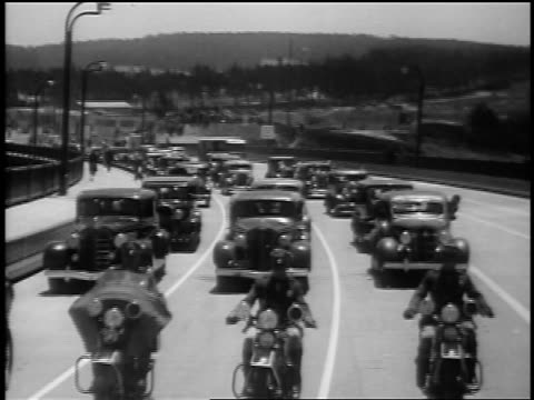 b/w 1937 tracking shot motorcade driving on golden gate bridge at opening / san francisco / newsreel - 1937 stock-videos und b-roll-filmmaterial