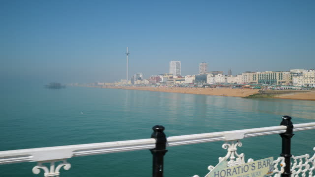 tracking shot moving along brighton's palace pier and looking back towards brighton beach. - sunny stock videos & royalty-free footage