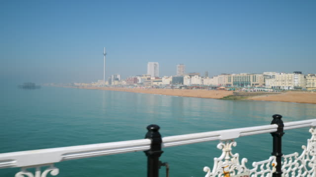 tracking shot moving along brighton's palace pier and looking back towards brighton beach. - brighton england stock videos and b-roll footage