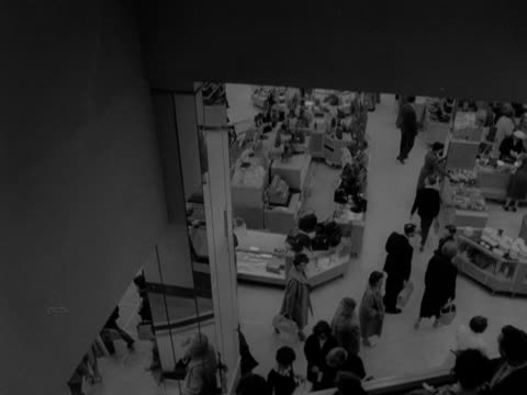 tracking shot moving down an escalator in a department store. shoppers browse the counters on the floor below. 1957. - department store stock videos & royalty-free footage