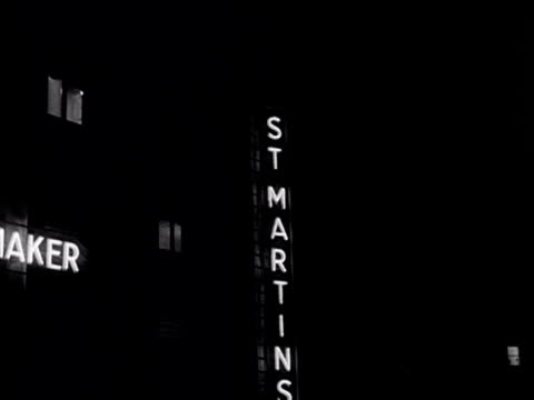 tracking shot moving past the neon sign for the st martins theatre on west street. 1956. - ウェストエンド点の映像素材/bロール