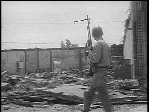 B/W 1965 tracking shot National Guard soldier passing destroyed buildings after Watts race riots low angle / newsreel