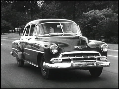 tracking shot of 1952 chevy styleline deluxe driving on urban highway / family in car: mom, boy, and dad montage: 1952 chevrolet styleline deluxe... - image montage stock videos & royalty-free footage