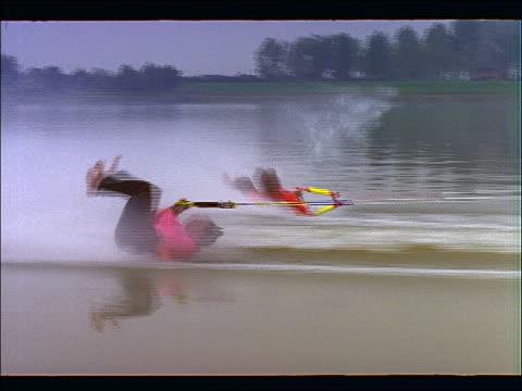 tracking shot of 2 men waterskiing barefoot + doing stunts - waterskiing stock videos & royalty-free footage