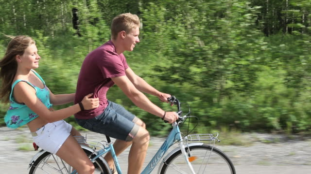 Tracking shot of 2 teens riding double on bike