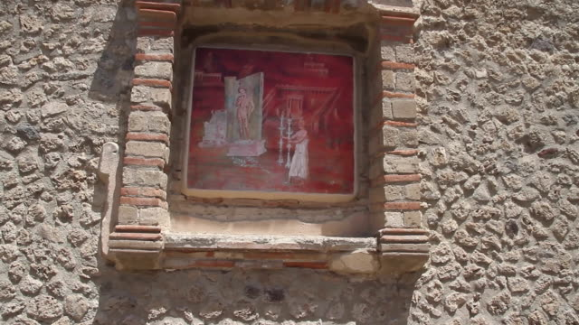 Tracking shot of a beautifully preserved mural or frescoe framed in stone on an ancient wall in the city of Pompeii, Napoli