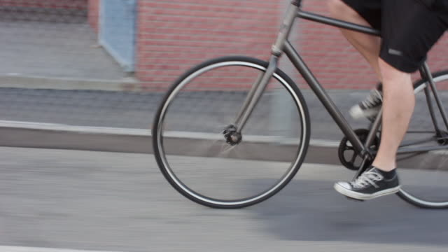 Tracking shot of a bicycle tire riding on a bike path by a creek.