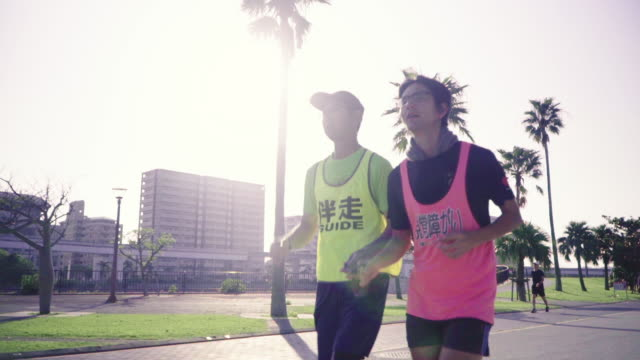 vidéos et rushes de tracking shot of a blind marathon athlete running with his guide - aveugle