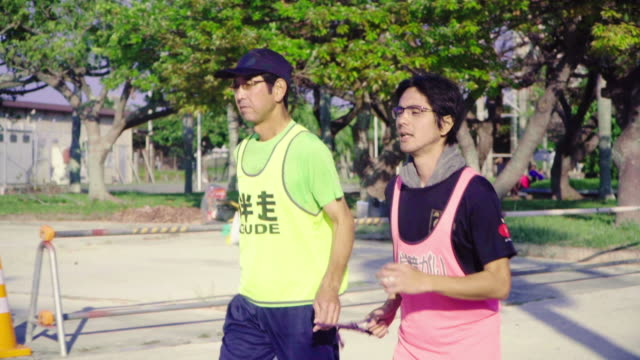 tracking shot of a blind marathon athlete running with his guide - visual impairment stock videos & royalty-free footage