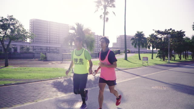 Tracking shot of a blind marathon athlete running with his guide