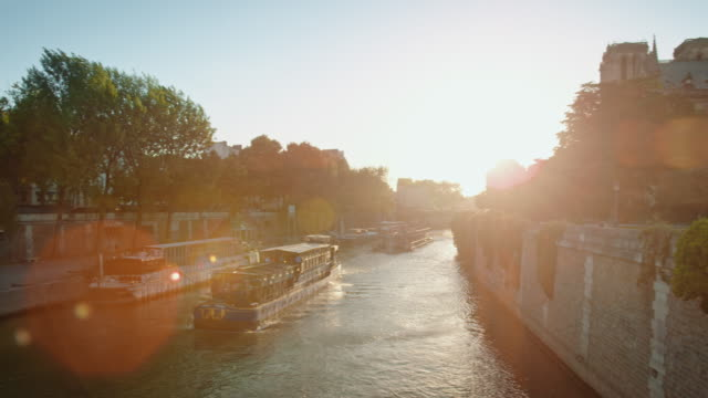 tracking shot of a boat on the seine river at sunset near notre-dame de paris - notre dame de paris stock videos and b-roll footage
