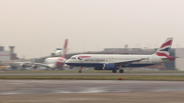 tracking shot of a british airways airbus a320 decelerating after landing on a runway at heathrow airport london - asphalt stock-videos und b-roll-filmmaterial