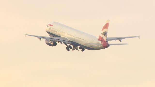 tracking shot of a british airways airbus a321 taking off at speed and landing gear retracting at heathrow airport, london - landefahrwerk stock-videos und b-roll-filmmaterial