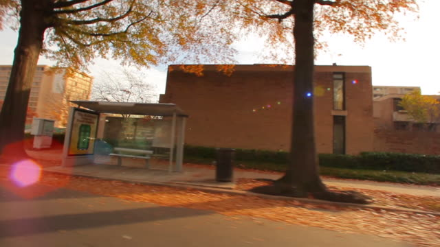 vidéos et rushes de tracking shot of a bus station bench in washington dc in autumn. - station