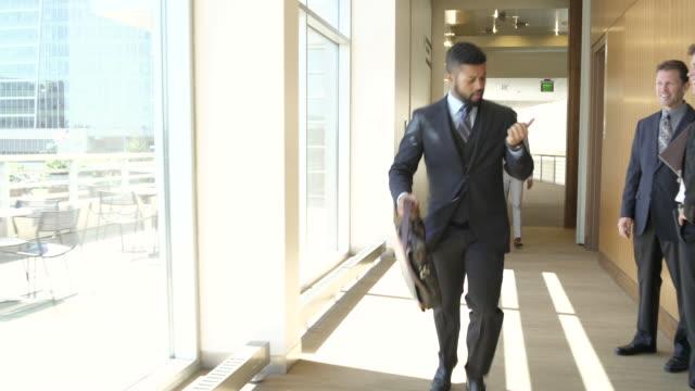 tracking shot of a businessman in a hurry - corridoio caratteristica di una costruzione video stock e b–roll