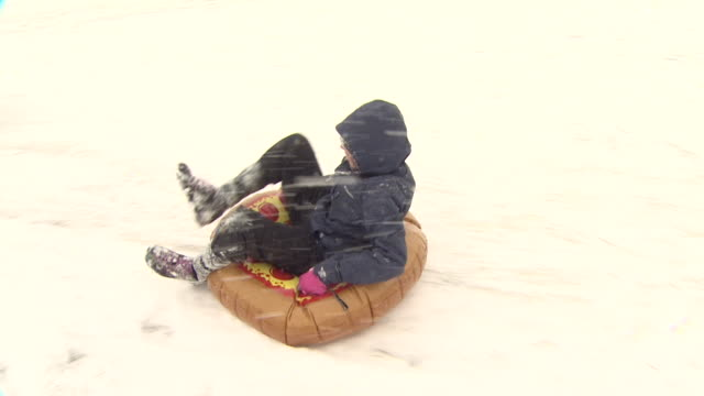 tracking shot of a child sleding down a snowy parliament hill, london - parliament hill stock videos & royalty-free footage