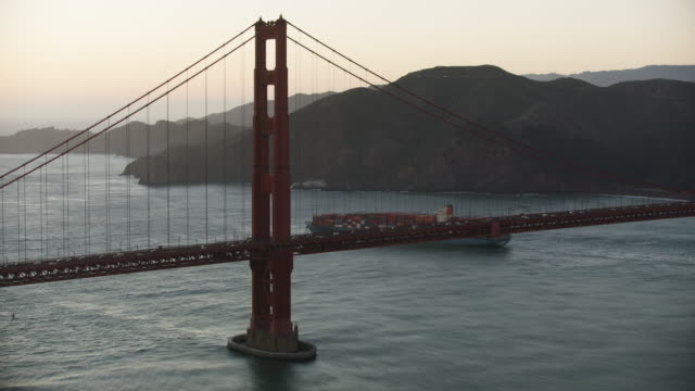 tracking shot of a container ship moving away from the golden gate bridge at dusk - bucht von san francisco stock-videos und b-roll-filmmaterial