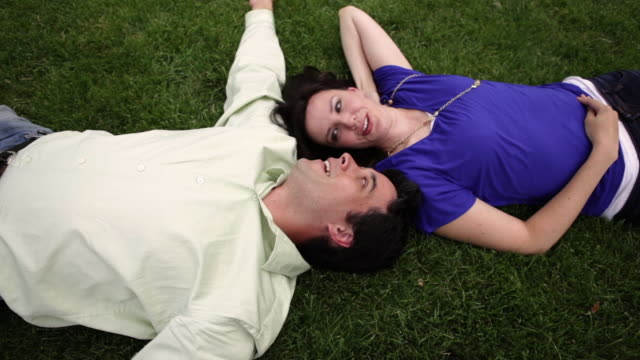 A tracking shot of a couple laying on the green grass next to each other.