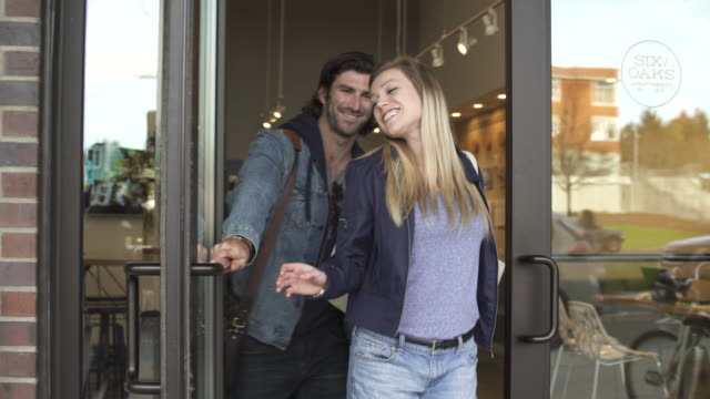 tracking shot of a couple leaving a building - halten stock-videos und b-roll-filmmaterial