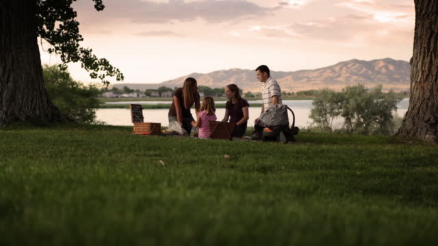 vidéos et rushes de a tracking shot of a family of five having a picnic on a beautiful green lawn. - pelouse