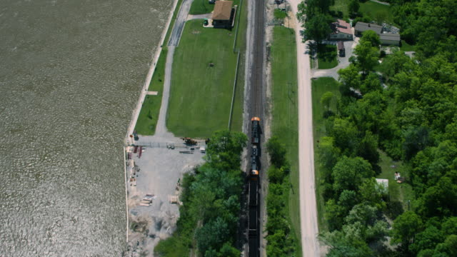 tracking shot of a freight train arriving to the station near the 22 lock on mississippi river - ミズーリ州点の映像素材/bロール