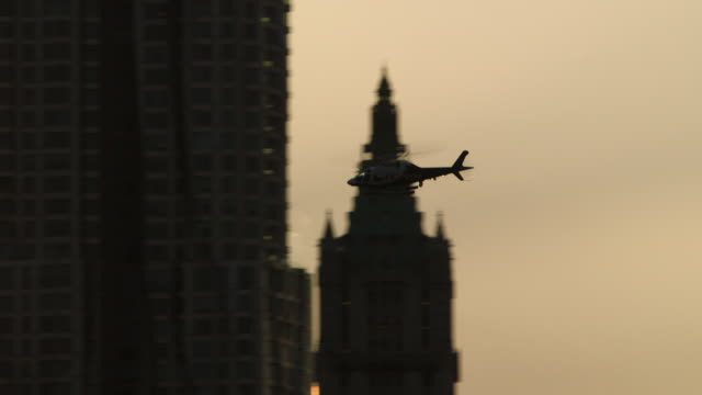 Tracking shot of a helicopter flying past the One World Trade Center finishing on the American flag.