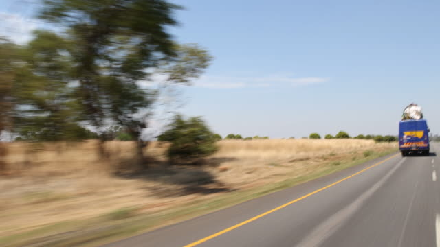 a tracking shot of a highway road with natural landscape and transportation vehicle overtaking a bus - overtaking stock videos and b-roll footage