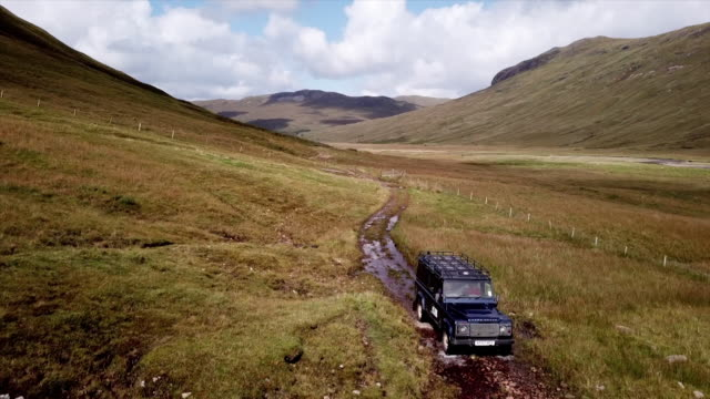 tracking shot of a land rover driving through the rolloing hills of the scottish highlands - schottisches hochland stock-videos und b-roll-filmmaterial