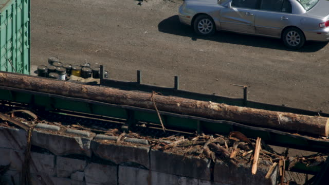 tracking shot of a log going through a debarker machine - lumberyard stock videos and b-roll footage