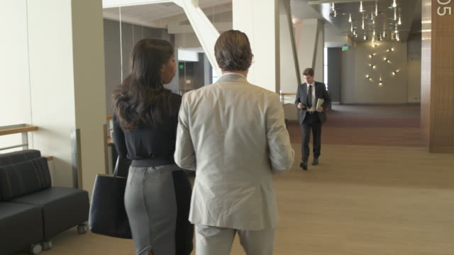 tracking shot of a man and a woman walking in a conference center - lobby stock videos & royalty-free footage