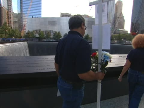 vidéos et rushes de tracking shot of a man carrying flowers as he looks for a name at the 9-11 memorial on 9/11/11, the tenth anniversary of the attacks. the memorial,... - mémorial