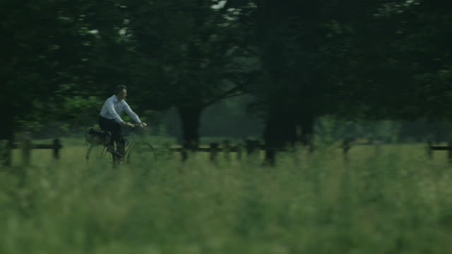 tracking shot of a middle-aged man in smart clothes cycling across stourbridge common in cambridge, uk. - mountain bike stock videos & royalty-free footage