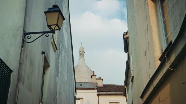 vídeos y material grabado en eventos de stock de tracking shot of a montmartre narrow street, sacré-coeur basilica in the background - basílica del sagrado corazón de montmartre