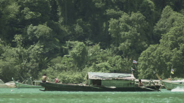 Tracking shot of a motorised fishing boat of the Moken people heading out to sea in Thailand.