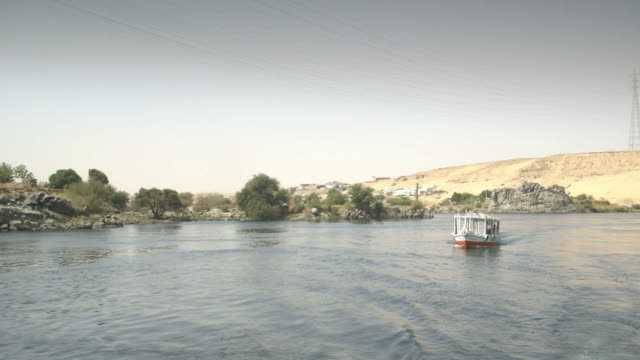 vidéos et rushes de tracking shot of a passenger boat as it travels along the river nile, egypt. - égypte