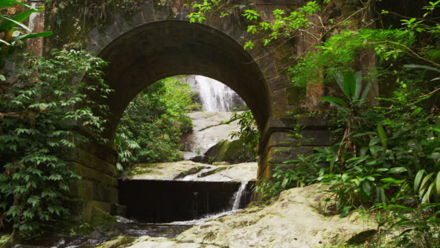 tracking shot of a scenic jungle stream flowing underneath a bridge arch. - arch bridge stock videos & royalty-free footage