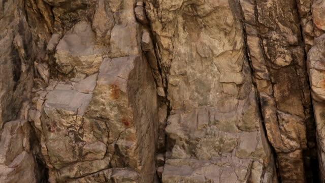 vídeos de stock, filmes e b-roll de tracking shot of a sheer rock face. - paredão rochoso