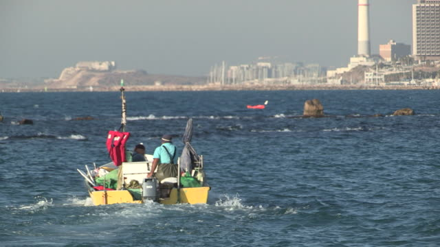 tracking shot of a small fishing boat heading out to sea - jaffa stock-videos und b-roll-filmmaterial