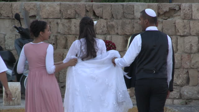 stockvideo's en b-roll-footage met tracking shot of a small wedding party walking away - jaffa