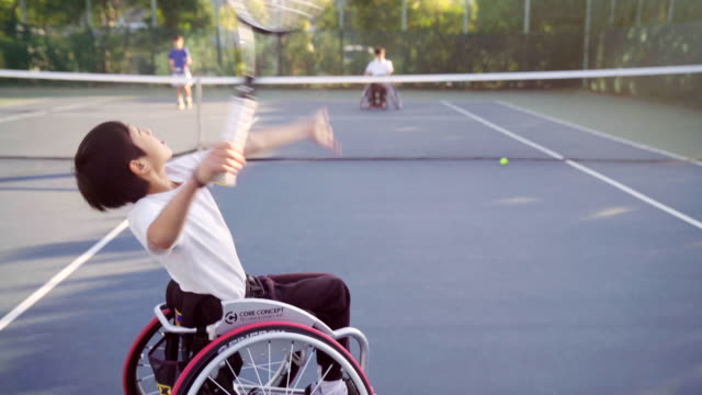 tracking shot of a teenage adaptive tennis player serving - drive ball sports stock videos & royalty-free footage