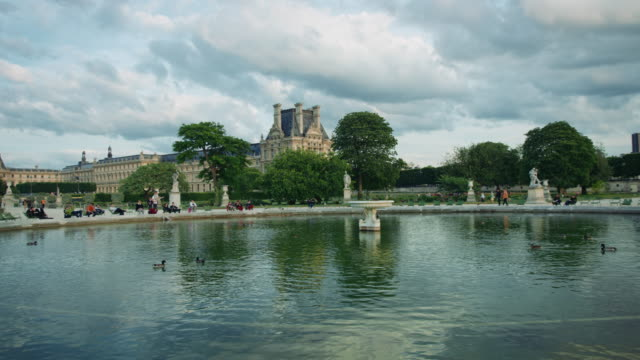tracking shot of a tuileries gardens fountain, musée du louvre in the background - medium group of animals stock videos & royalty-free footage