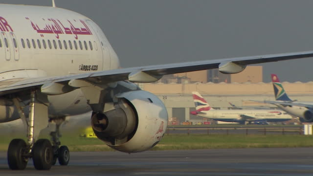 tracking shot of a tunisair airbus a320 moving slowly on a runway at heathrow airport, london - tunisia stock videos & royalty-free footage