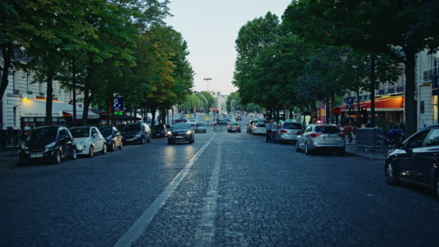 tracking shot of a typical paris avenue - kopfsteinpflaster stock-videos und b-roll-filmmaterial