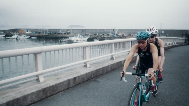 tracking shot of a visually impaired female triathlete training together with her guide and coach on a tandem bicycle - visual impairment stock videos & royalty-free footage