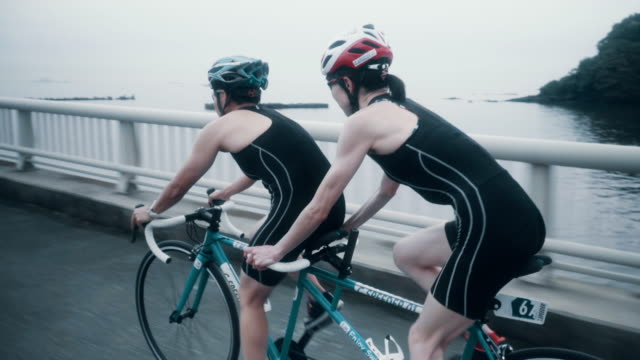 tracking shot of a visually impaired female triathlete training together with her guide and coach on a tandem bicycle - only japanese stock videos & royalty-free footage